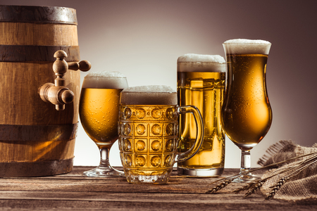 barrel and assortment of beer in glasses on wooden tabletop with wheat ears Фото со стока