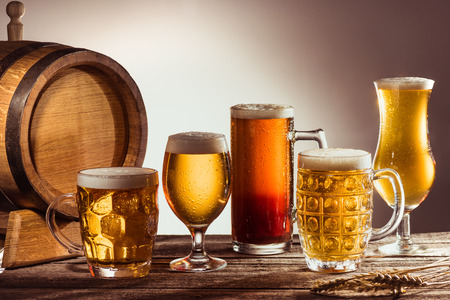 barrel and assortment of beer in glasses on wooden tabletop with wheat ears Stok Fotoğraf - 89721864