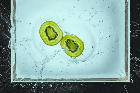 fresh kiwi slices floating in water with splash