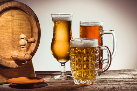 barrel and different beer in glasses