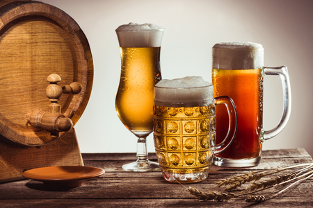barrel and different beer in glasses on wooden tabletop with wheat ears Banco de Imagens - 89711708