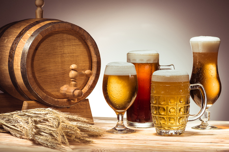 barrel and different beer in glasses on wooden tabletop with wheat ears