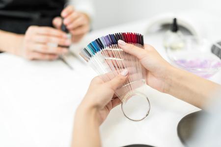 cropped shot of woman choosing nail polish color in beauty salon