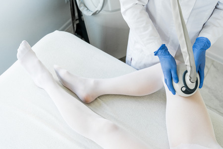cropped shot of woman having procedure of lipomassage in apparatus cosmetology clinic