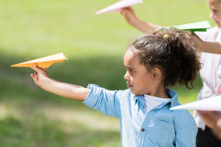 紙飛行機で遊んでいる子供たち