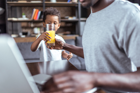 son giving orange juice to father
