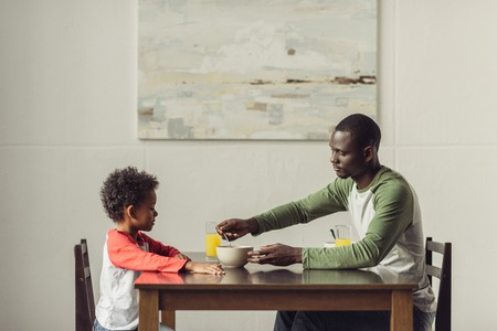 father and son eating breakfast Stock Photo - 89867050