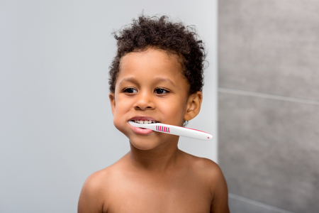 afro kid brushing teeth Stock Photo