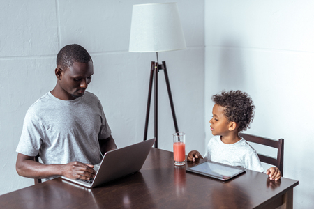 father and son using laptop and tablet