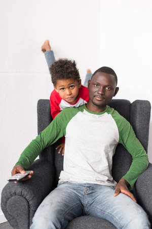 father and son watching tv Stock Photo - 89865516