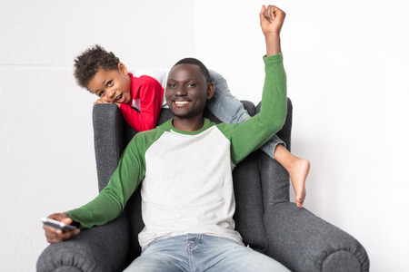 father and son watching tv Stock Photo - 89865189