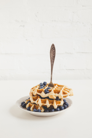 stack of waffles with blueberries pierced with fork