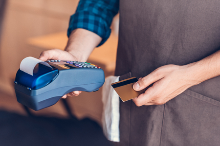 partial view of barista holding credit card and cardkey reader in hands in cafe Imagens