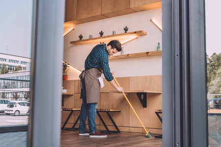 worker cleaning floor with sweep Foto de archivo
