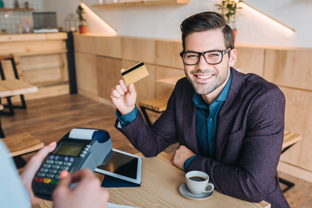 Empresario pagando con tarjeta de crédito en café Foto de archivo - 89856427