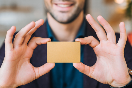 Partial view of smiling businessman showing blank business card in hands in cafe
