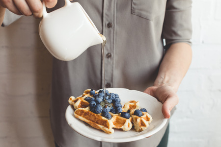 cropped shot of woman pouring maple syrup on tasty waffles Stok Fotoğraf - 89789614