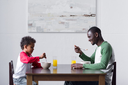 father and son eating breakfast Stock Photo - 89856050