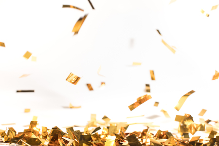 falling pieces of golden confetti on white
