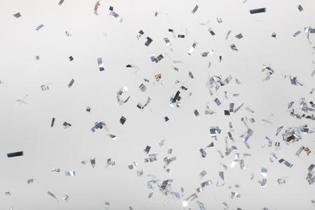 Caer piezas de confeti plateado en gris