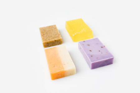 various colorful handcrafted soap on white surface