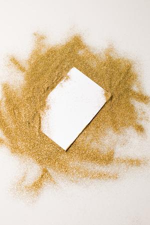 Bovenaanzicht van wit vel papier in verspreide gouden glitter Stockfoto