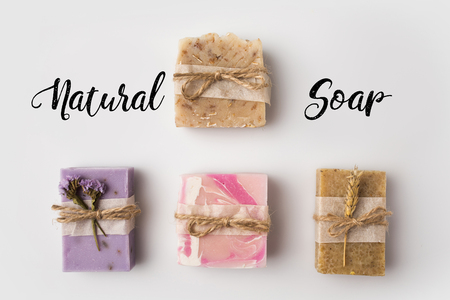 top view of different handcrafted soap with natural soap lettering on white surface 스톡 콘텐츠