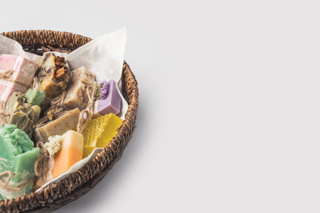 lavender coloured: close-up shot of various handcrafted soap in bowl on white surface Stock Photo