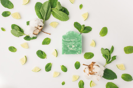 top view of handcrafted green soap with mint leaves and lime slices on white surface