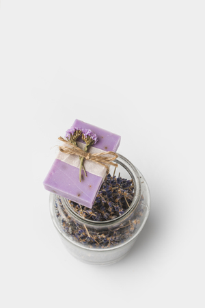 top view of aromatic handcrafted lavender soap with jar of flowers on white surface