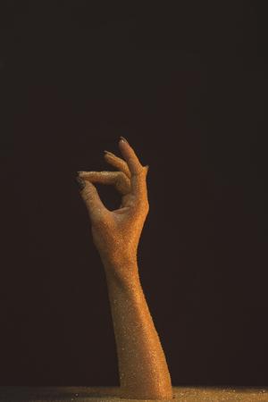 Was hand in gouden lovertjes met duim aanrakende middelvinger