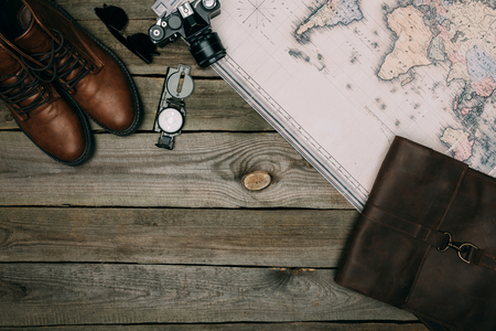 Top view of map, film camera with compass and shoes on a wooden table, travel concept Imagens