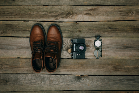 Flat lay of brown shoes with film camera and compass on a wooden table Imagens