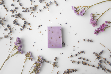 top view of handcrafted purple lavender soap with flowers around on white surface Stock Photo