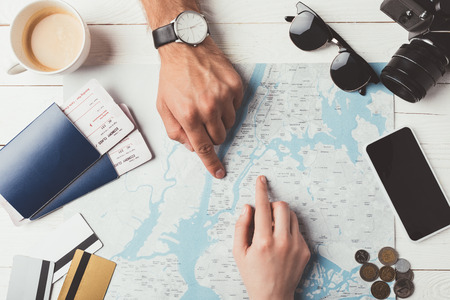 couple of travelers showing something on a map at the table  Stockfoto