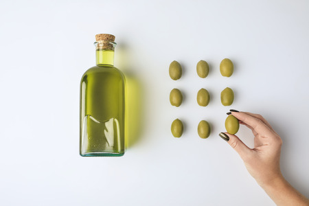 Cropped image of woman holding one olive and bottle of olive oil isolated on white