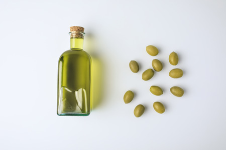 Top view of glass bottle with olive oil and green olives isolated on white