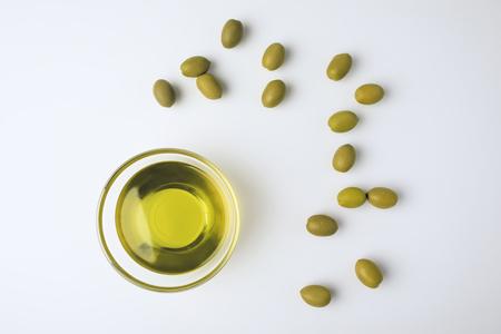 Hoogste mening van glaskom met olijfolie en verspreide groene olijven die op wit worden geïsoleerd
