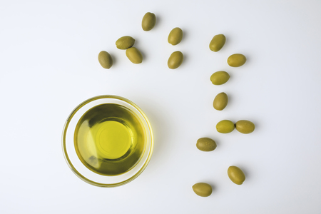 Top view of glass bowl with olive oil and scattered green olives isolated on white