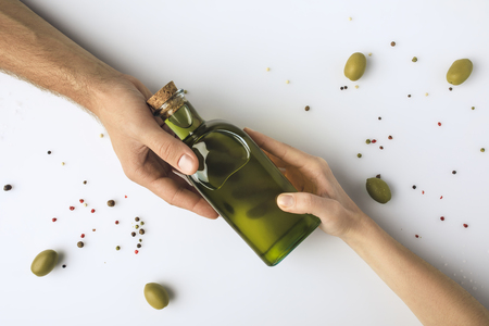 Cropped image of man and woman holding olive oil bottle in hands isolated on white