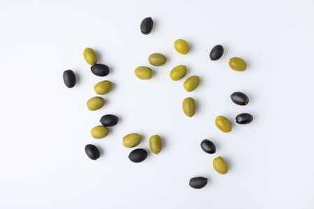 Top view of scattered unprocessed green and black olives isolated on white