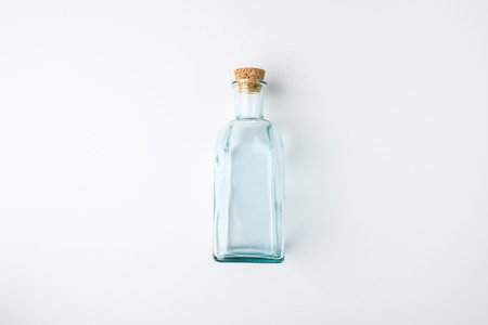 Top view of transparent glass bottle with cork isolated on white