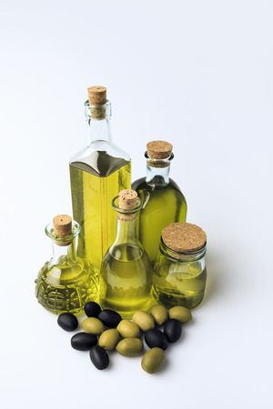 Different glass bottles with homemade olive oil and olives isolated on white