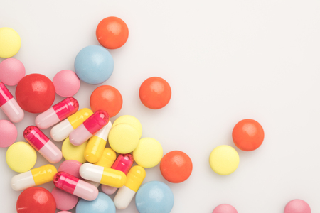 top view of scattered pile of colored pills isolated on white