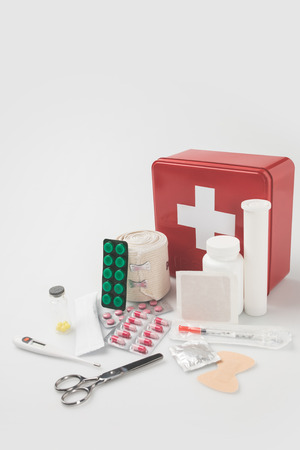 first-aid kit with blister packs with pills, thermometer and elastic bondage isolated on white  Stock Photo
