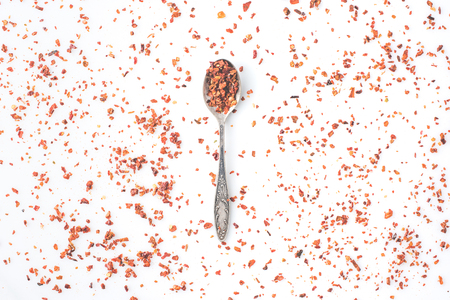 top view of spoon with grated red pepper isolated on white