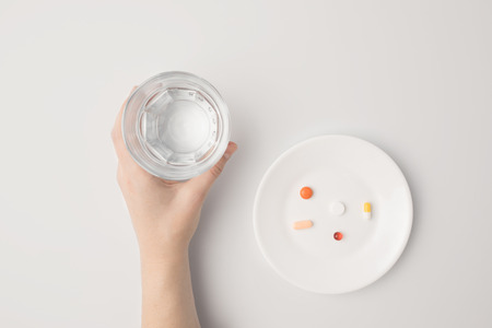 Cropped image of woman holding glass of water, different pills on a plate