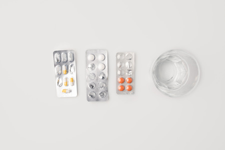Top view of half empty blister packs with pills and glass of water