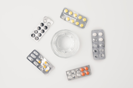Top view of glass of water inside of circle of blister packs with different pills