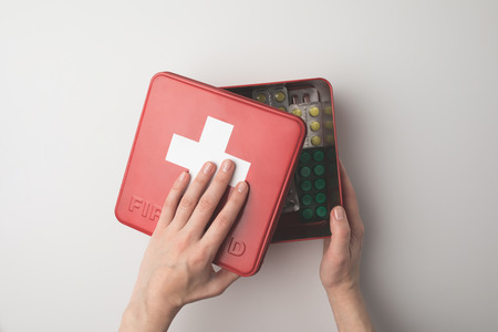 Top view of first-aid kit with blister packs with pills inside